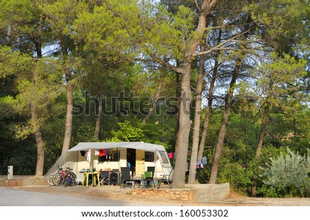 Camping in France; caravan with an awning between trees - stock photo