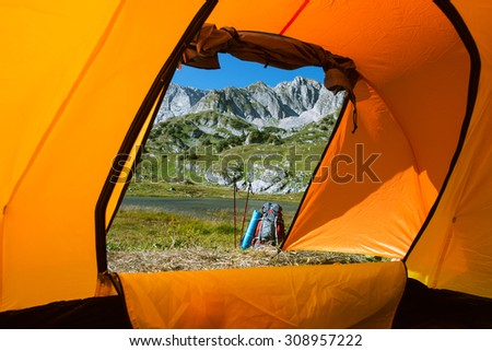 camping in mountain lake with backpack and  Nordic walking sticks - stock photo