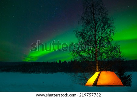 Camping in the north with the northern lights overhead - Aurora Borealis - stock photo