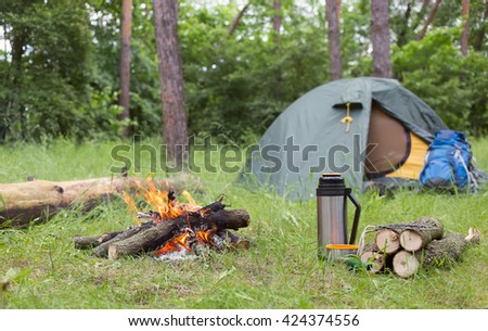 Camping in the woods with a fire in a clearing. - stock photo