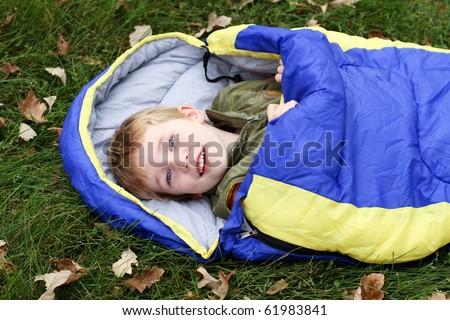 Camping kid in sleeping bag - stock photo