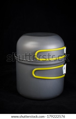 Camping pan with cover with folding handles, isolated on black background - stock photo