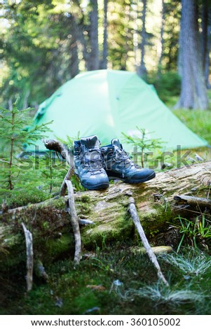 Camping people putting on hiking shoes by tent - stock photo
