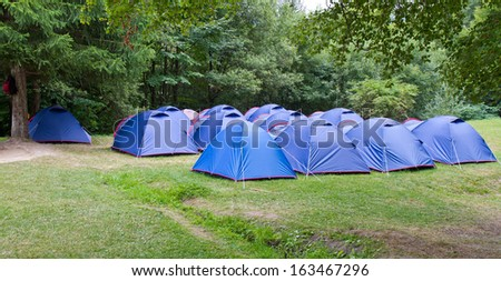 Camping site with blue tents set up - stock photo