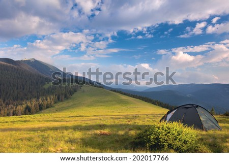 Camping tent in the mountains. Summer, blue sky, clouds and high peaks. It is dream - stock photo