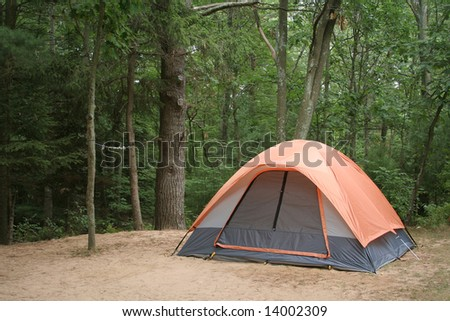 CAMPING TENT IN WOODS - stock photo