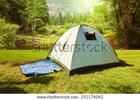 Camping tent on grass over beautiful forest - stock photo