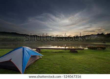 Camping tent on green grass beside lake with foggy over forest during sunrise, Thailand