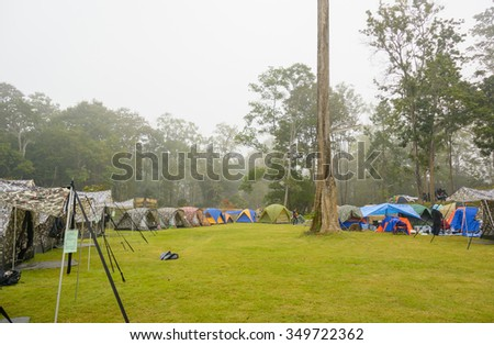 camping tent on green grass field at morning fog natural