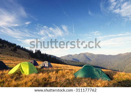 camping tents on the meadow after sunrise, mountains on background - stock photo