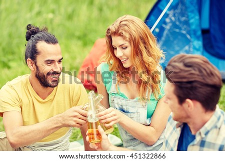 camping, travel, tourism, hike and people concept - happy friends with glass bottles drinking cider or beer at campsite - stock photo