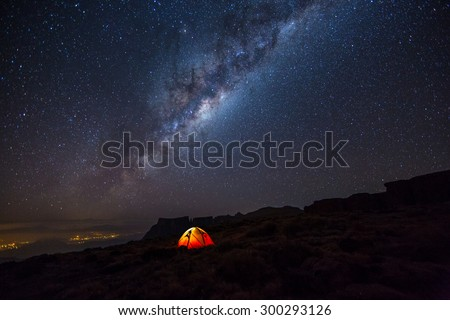 Camping under the stars. The Milky Way stretches overhead the tent high above the villages in the Drakensberg mountains, on the Amphitheatre. - stock photo