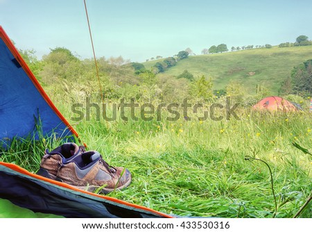 Camping, View from inside a tent with walking boots looking at another tent on a campsite field.                        - stock photo