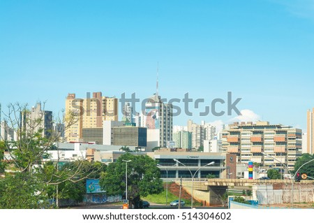 Campo Grande, MS, Brazil - November 10, 2016: Landscape of the city of Campo Grande. City with some buildings between trees, car traffic and urban art.