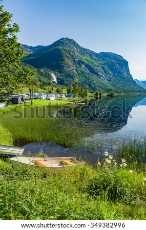 Campsite by the lake and mountains reflection on the water - stock photo