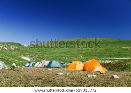 Campsite with a variety of multi-colored tourist tents. The concept of a group holiday among of pristine alpine summer meadows