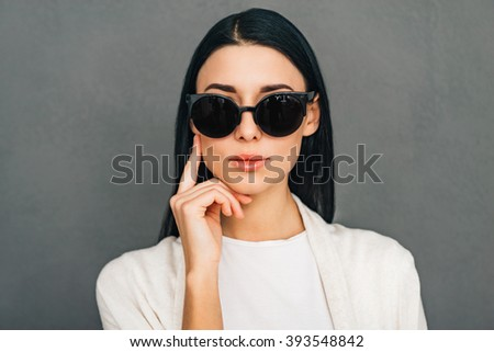 Can not take my eyes of you! Portrait of beautiful young woman in sunglasses looking at camera while standing against grey background