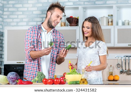 Can we add the cucumber. Young and beautiful couple in love prepared vegetables and help each other while breakfast is prepared with vegetables in the kitchen. - stock photo