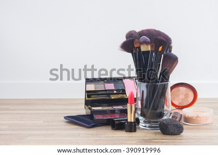 can with  brushes and make up products on wooden table with copy space - stock photo