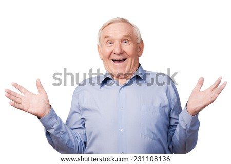 Can you believe that!  Excited senior man gesturing and smiling while standing against white background  - stock photo