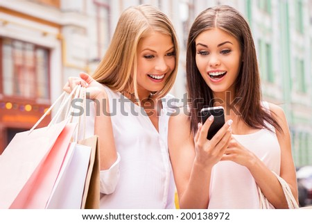 Can you imagine that? Two surprised young women holding shopping bags and looking at mobile phone together while standing outdoors - stock photo
