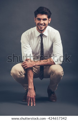 Can you resist his smile? Full length of confident young handsome man looking at camera with smile while sitting crouched against grey background - stock photo