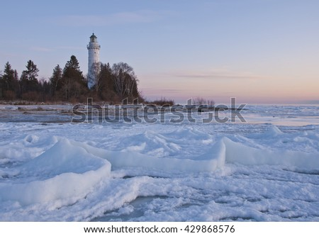 Cana Island Lighthouse sits in pre dawn Light it's lantern having just gone off and the sun is about to rise in the sky, Cana Island, Door County, Wisconsin - stock photo
