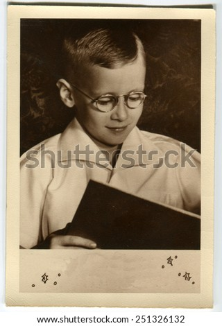 CANADA - CIRCA 1940s: Reproduction of an antique photo shows Portrait of a boy with glasses reading a book - stock photo