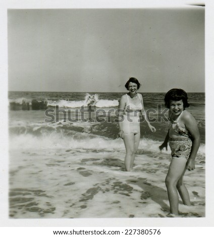 CANADA - CIRCA 1950s: Vintage photo shows mother and her daughter swimming in the sea. - stock photo