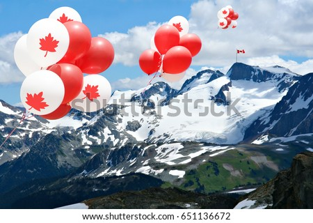 Canada day Maple leaf balloons floating over the Rocky mountains with a Canadian flag in the distance.