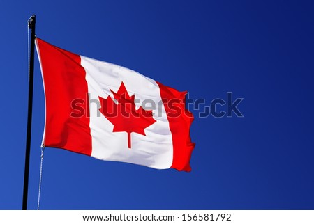 Canada flag on blue sky - stock photo