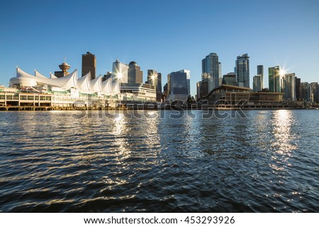 Canada Place, Convention Centre and Buildings in Downtown Vancouver, BC, Canada, viewed from water during a sunset.
