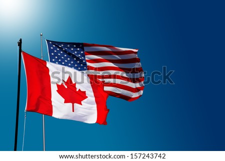 Canadian and USA flag on blue sky - stock photo