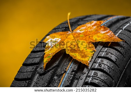 Canadian Car tire with maple leaf in autumn and raindrops - stock photo