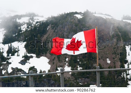 Canadian flag blowing in the wind in the alpine. - stock photo