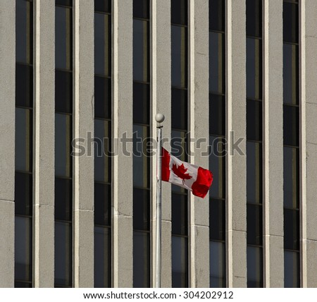 Canadian flag flies against the background of an office building.