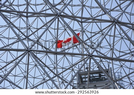 Canadian flag flying inside the geodetic dome of the Biosphere in Montreal, Canada - stock photo