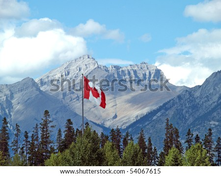 Canadian flag in the Rockies - stock photo