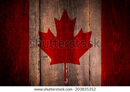 Canadian flag over a grunge wooden background. - stock photo