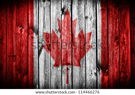canadian flag painted on old wood plank background - stock photo
