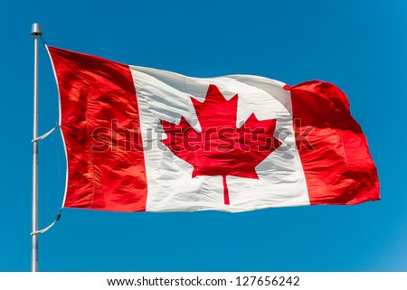 Canadian flag waving in the air over a beautiful blue sky - stock photo