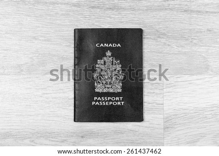 Canadian Passport on a wood floor in black and white - stock photo