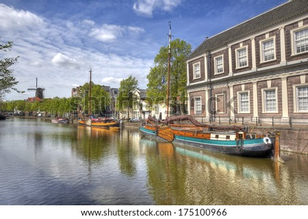 Canal and historical boats, windmill in the distance in Schiedam, Holland - stock photo