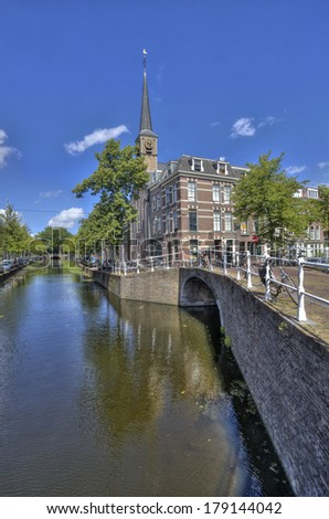 Canal, bridge, houses and tower of small church in Delft, Holland - stock photo