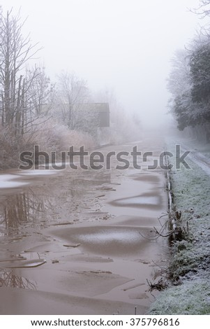 Canal building covered in frost on a cold and foggy Winters day - stock photo
