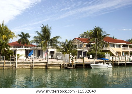 canal channel with boats and houses florida keys typical architecture scene - stock photo