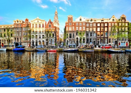 Canal houses of Amsterdam at dusk with vibrant reflections, Netherlands - stock photo