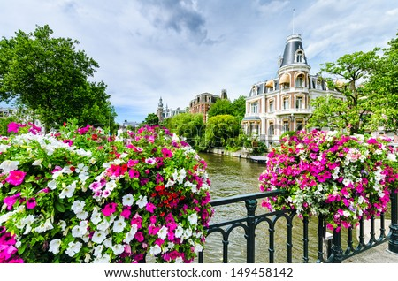 Canal in Amsterdam with flowers on a bridge - stock photo