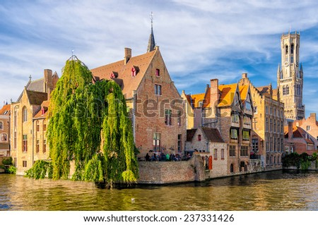 Canal in Bruges with the famous Belfry tower on the background. - stock photo