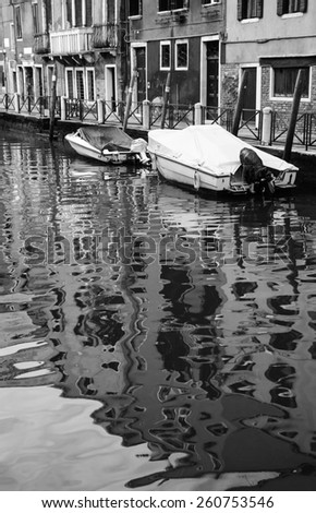 Canal in Venice. Boats and reflection of houses in the water. Aged photo. Black and white. - stock photo